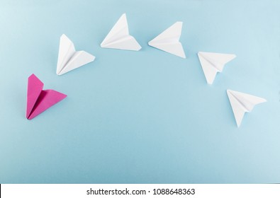 One Unique Pink Paper Plane among Many Ones. Different Paper Airplanes as Individuality and Leadership Concept