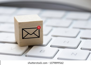 One unread e-mail message concept with computer keyboard and e-mail symbol on wooden cube