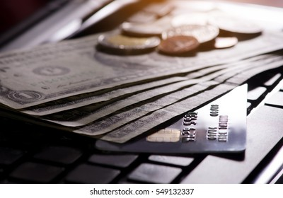 One US dollar bills,credit card,coins and computer.Dark tone business and finance concept background.