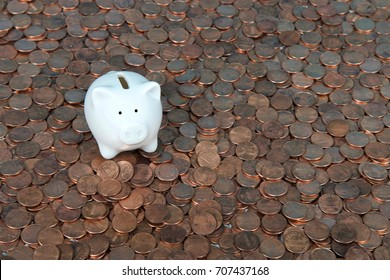 One very small white piggy bank sitting on a landscape of old and new pennies. With the collapse of the zinc market, the penny has become cheaper to make, costing the taxpayer much less.