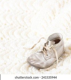 One Vintage Leather Infant's Shoe on a Hand Knitted  Cream Afghan Background with room or space for copy, text, your words.  Square crop, high key with white warm tones