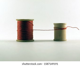 One Vintage Wooden Thread Spool With Red Thread Connected to an Empty Smaller Vintage Wooden Thread Spool