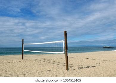 One volleyball net stands on a sandy beach near the ocean