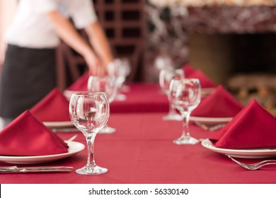 One of waiters is serving dinner place in a restaurant