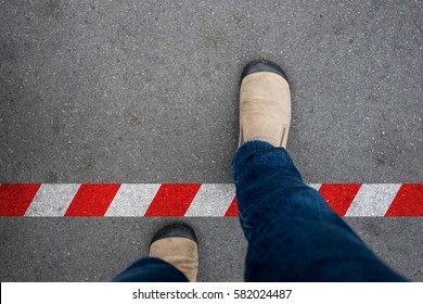 One walking across red and white line to prohibited area. Breaking the rule beyond the limit.