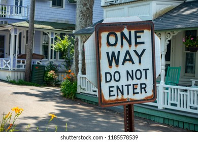 one way do not enter black & white sign with rusted edges on a summer suburban street in middle America homes with big white porches