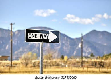 One way road sign with blurred mountains background.