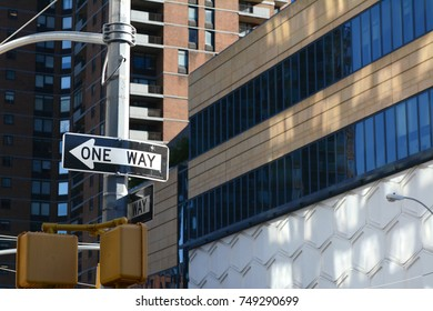 ONE WAY road sign points left on a New York City street, with high rise buildings beyond