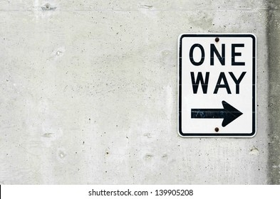 One Way Sign and Arrow on Concrete