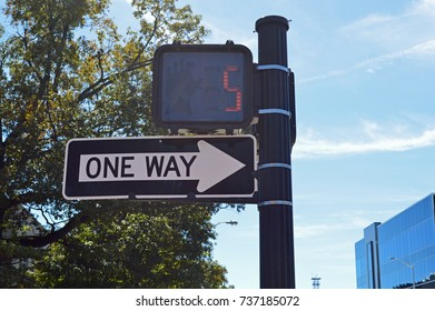 One way sign below pedestrian signal with 5 seconds left to walk