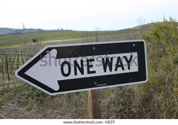 one way sign near farmers' fields