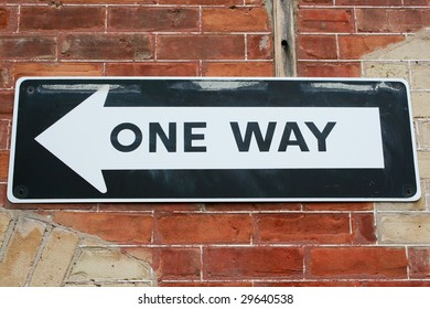 A one way sign on a brick wall