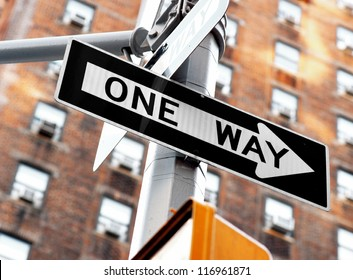 """""""one way"""" sign on pole in street in u.s.a."""