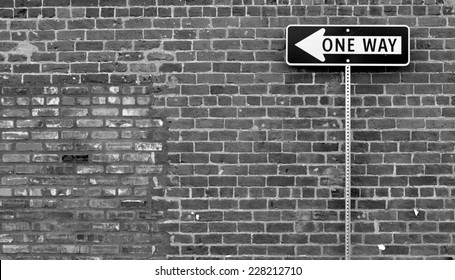one way street sign in front of brick wall