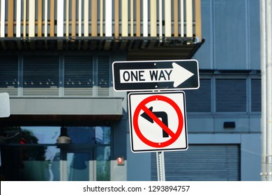 One way street sign n Manhattan, New York City, USA and Do not turn left traffic sign on white.