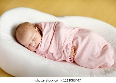 One week old newborn baby girl sleeping wrapped in blanket