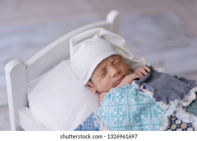 One week old newborn baby boy wearing a white sleeping cap. He is sleeping on a tiny, white bed and covered with a blue, patchwork quilt.