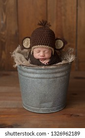 One week old newborn baby boy wearing a brown, crocheted monkey hat. He is sleeping in a galvanized steel bucket. Shot in the studio on a wood background.