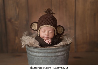 One week old newborn baby boy wearing a brown, crocheted monkey hat. He is sleeping in a galvanized steel bucket and has a slight grin on his face.