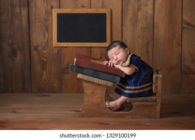 One week old newborn baby girl wearing a dress and sleeping on a stack of vintage books at a tiny school desk.