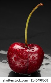 One wet cherry on black background.