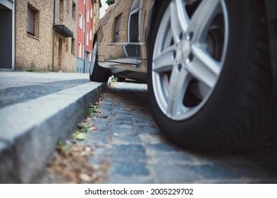 one wheel on curb, bad parking on a sidewalk