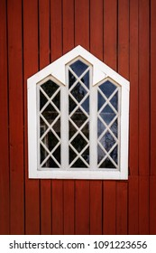 One white decorative traditional window with wooden frame on a red barn wall.