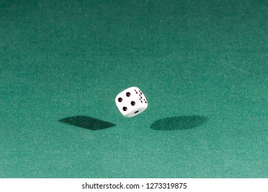 One white dice falling on a isolated green table