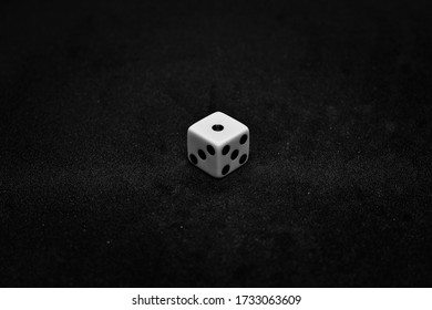 One white dice showing one on black background