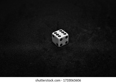 One white dice showing six on black background