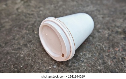 One white discarded paper cup is lying on the ground