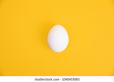 One white egg on yellow background. Creative minimal concept.