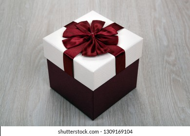 one white gift box with a bow on a gray wooden background close up