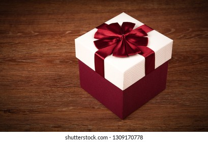 one white gift box with red bow on a wooden background close up