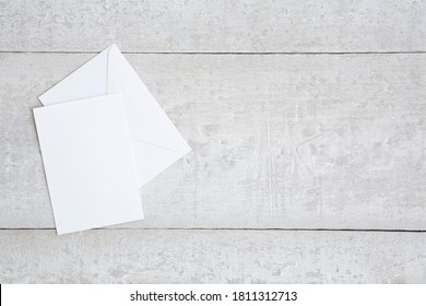 One white greeting card mockup on a white wooden desk. Blank, closed card template with envelope. Flat lay.