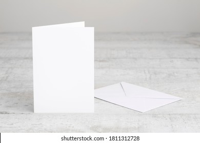 One white greeting card mockup with envelope, standing upright on a white wooden desk. Blank, closed card template.