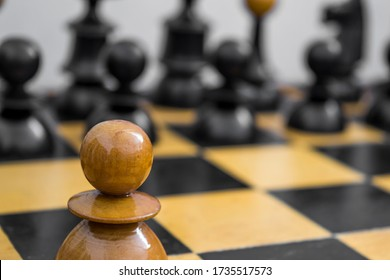One white pawn stands in front of all enemy chess figures, defiance concept
