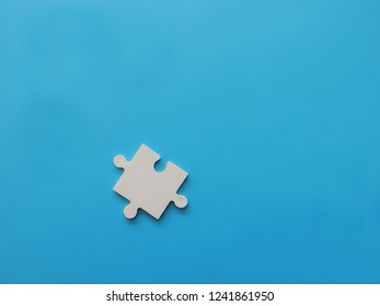 One white piece puzzle jigsaw on blue background.