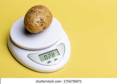 one white potato is weighed on a scale. background yellow