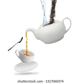 one white tea pot pours tea into a mug and spoon isolated on white background