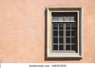 One white window of an orange ancient building