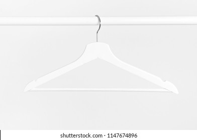 One white wooden hanger without clothes on background of white wall. Soft focus. Store concept, sale, design, empty hanger.