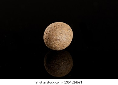 One whole brown clay pebbles (leca) isolated on black glass