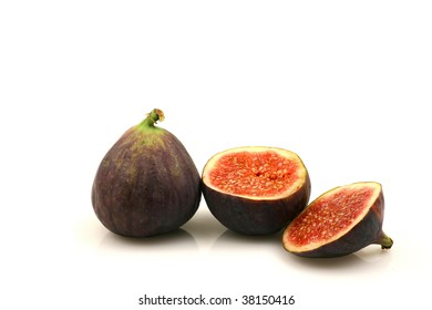 one whole and one cut fig on a white background