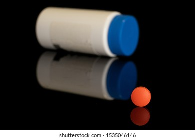 One whole orange tablet pharmacy with plastic bottle isolated on black glass