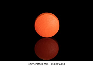One whole orange tablet pharmacy isolated on black glass