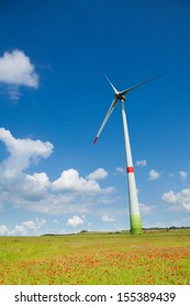 One wind turbine in the green field with poppy flowers on clean sky sunny day