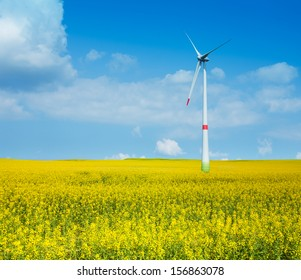 One wind turbine in the yellow flowers meadow on clean sky sunny day
