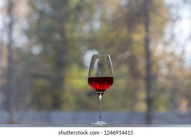 One wine glass with the red wine on a sill. The background is blurred.