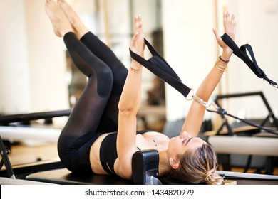 One woman in black outfit lying on her back doing supine arm work on pilates bed